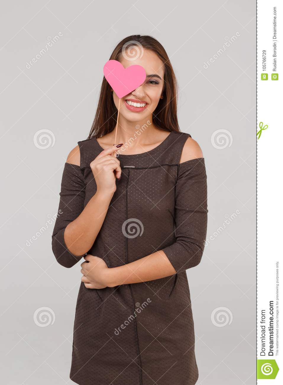 Young beautiful girl with a little pink heart on her eyes on a grey background. Valentine`s concept.