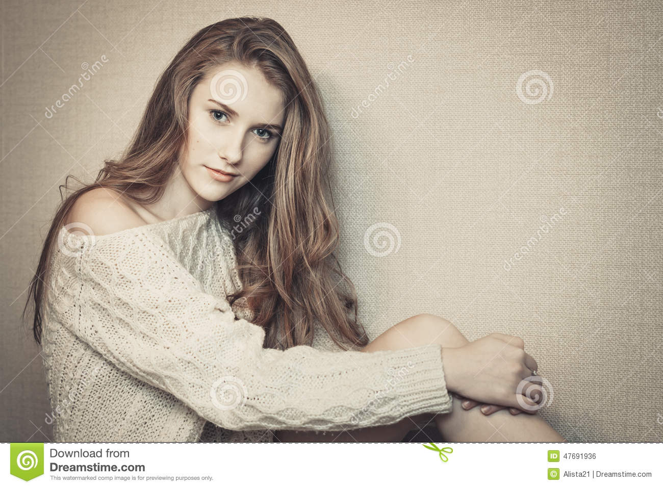 young beautiful girl with long curly hair sitting and posing in