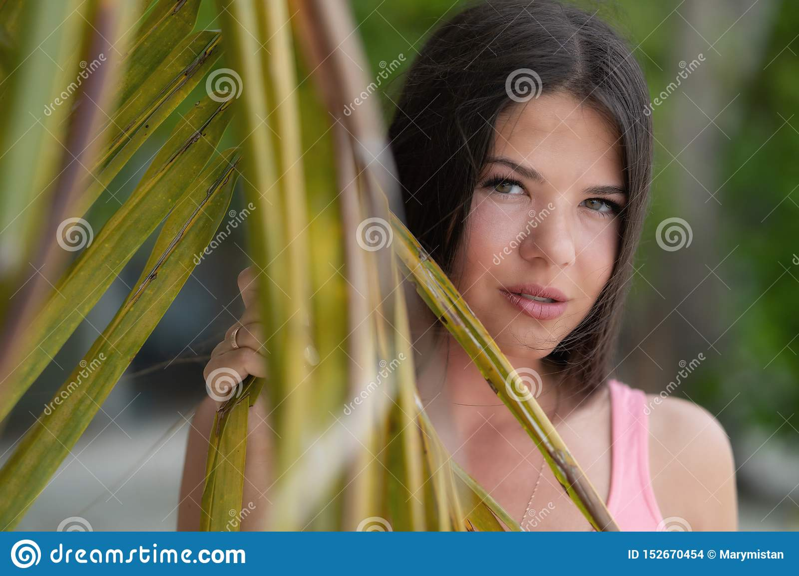 Young beautiful girl looks through a large leaf of a palm tree