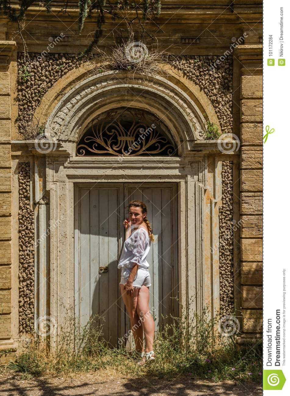 Young beautiful girl at the old door near the Villa Pamphili in Rome, Italy