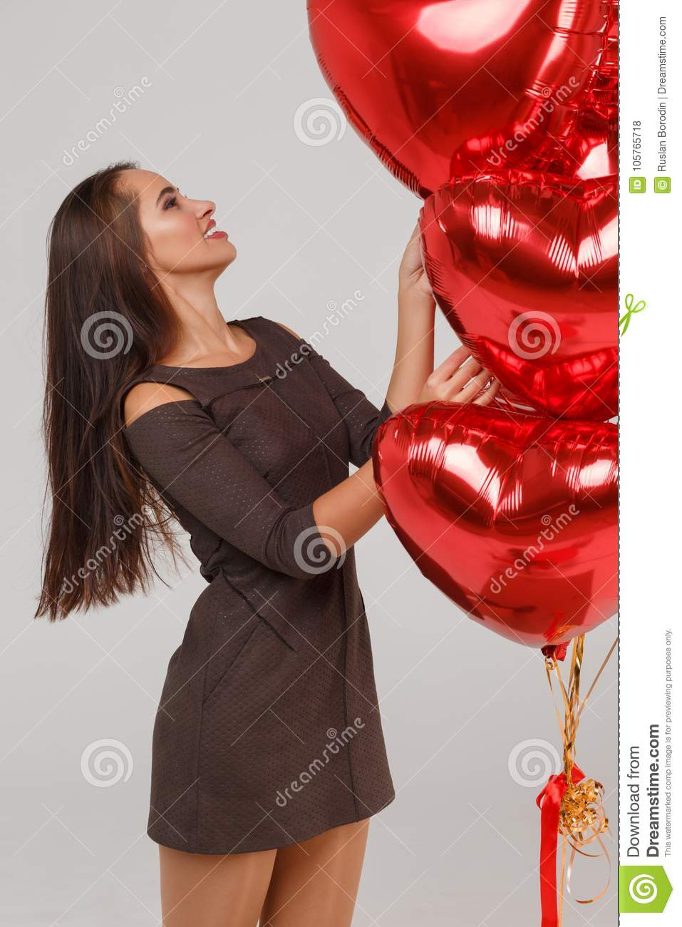 Young beautiful girl with red air balloons on a grey background. 8 March concept.