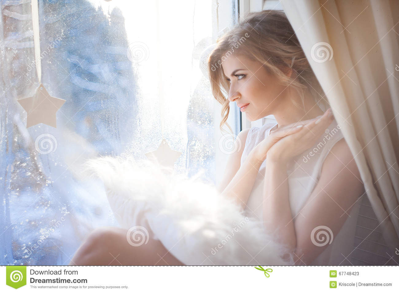 Young beautiful girl sitting on the windowsill, looking out window, morning light, glare