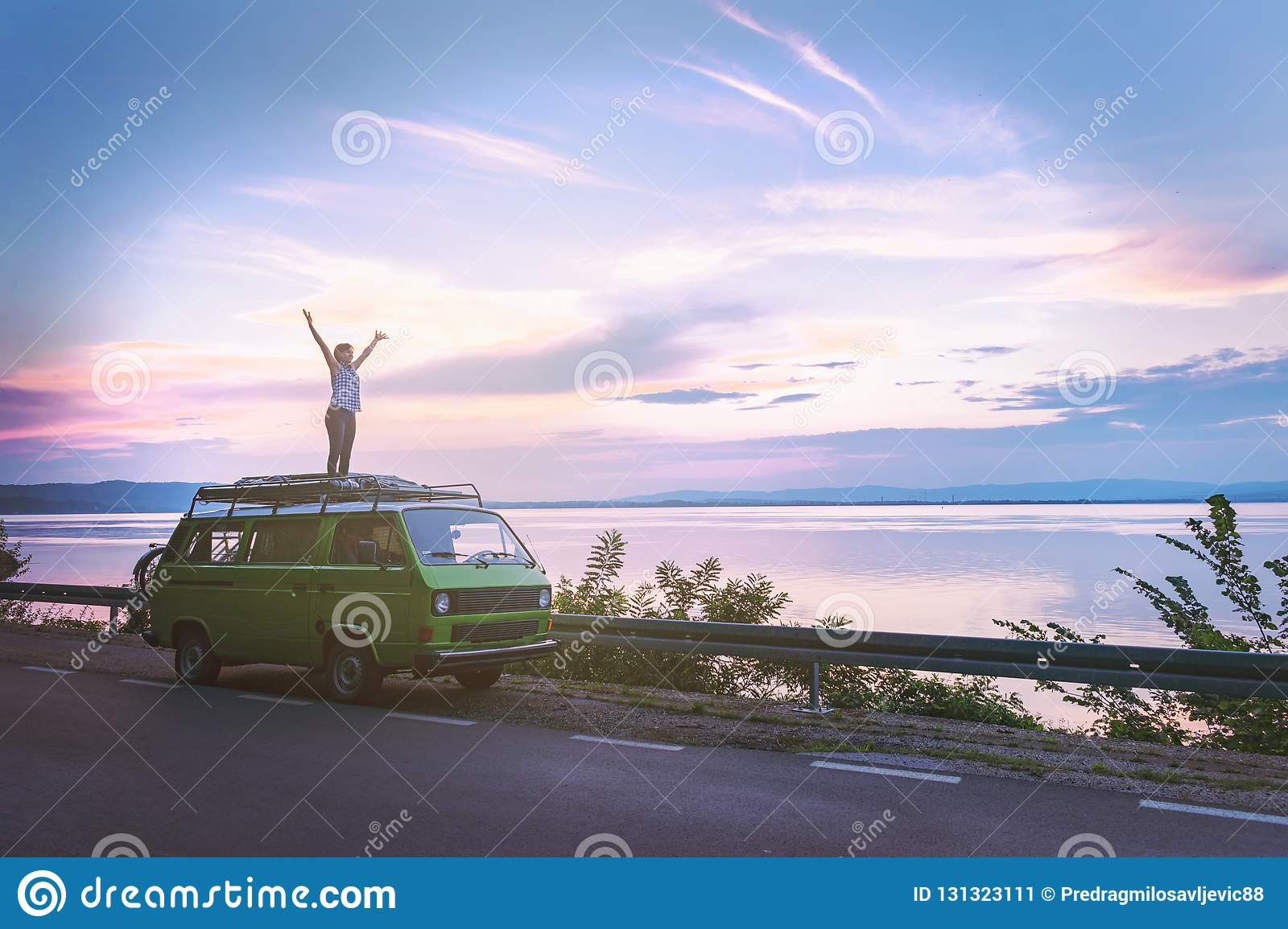 Young beautiful girl standing on the roof of old timer classic camper van parked by the sea with amazingly colorful sunset sky, ha