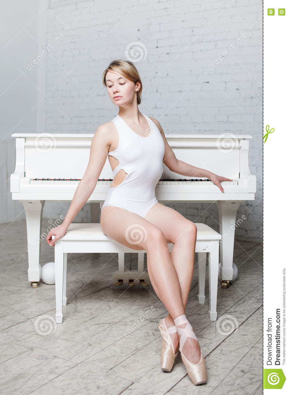0df6e243e Young Beautiful Girl In White Dance Leotard And Pointe Shoes
