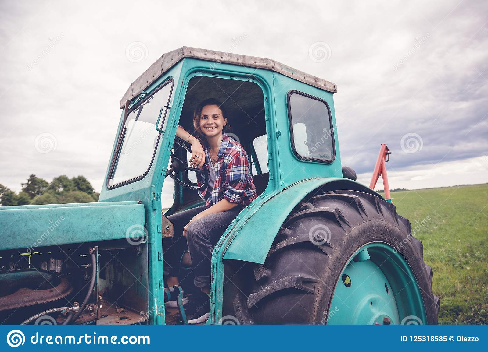 Young beautiful girl working on tractor in the field, unusual work for women, gender equality concept