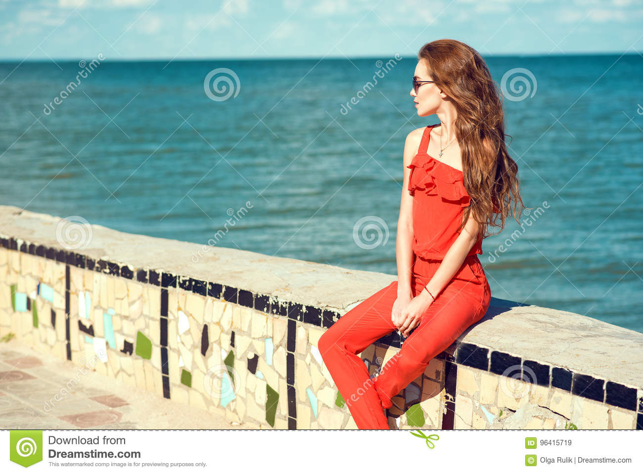 Young beautiful glam stylish woman wearing coral red jumpsuit and dark trendy sunglasses sitting on the parapet at the seaside
