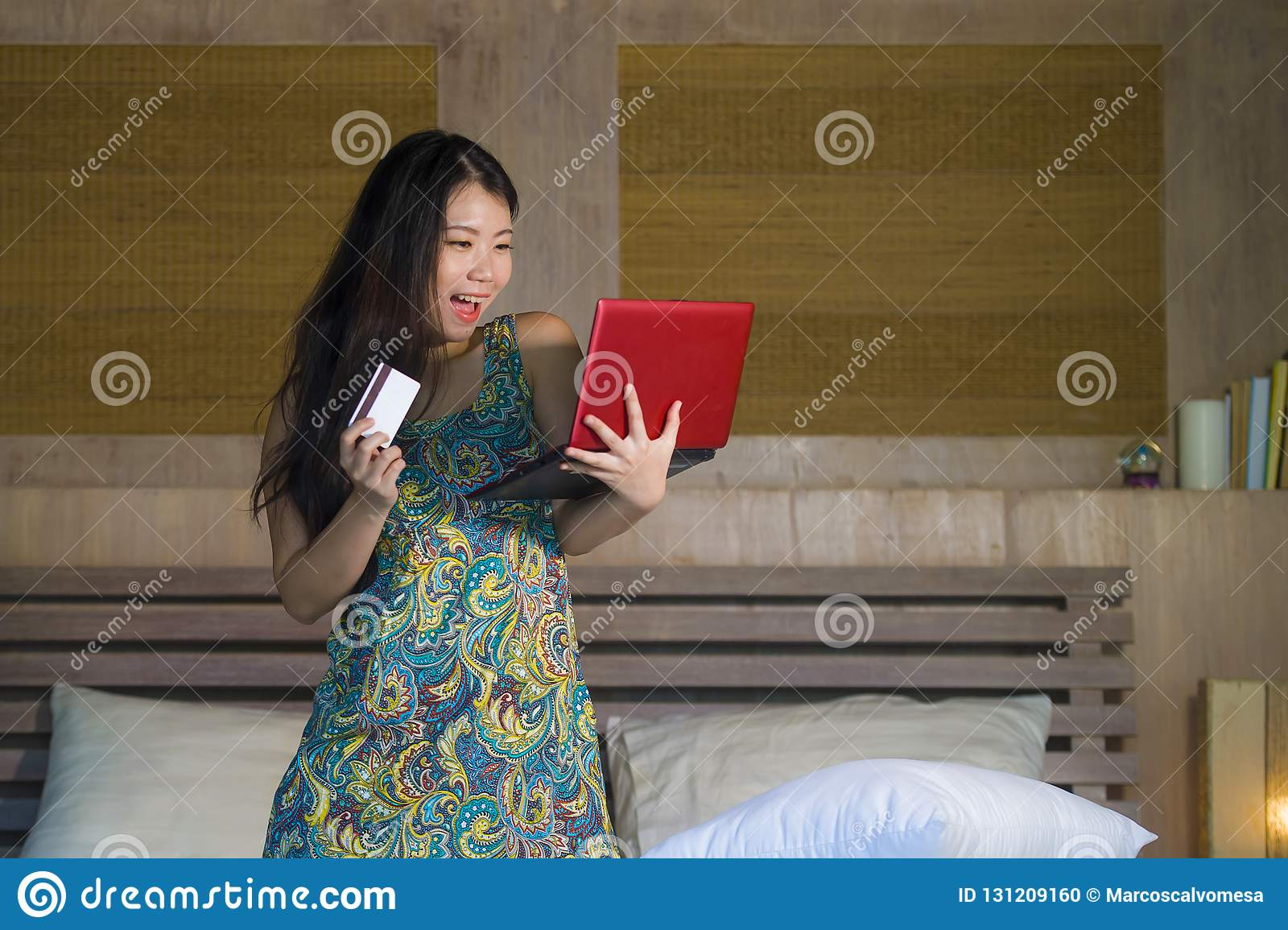 Young beautiful happy Asian Japanese woman using credit card internet banking on laptop computer at home in bed shopping online e-
