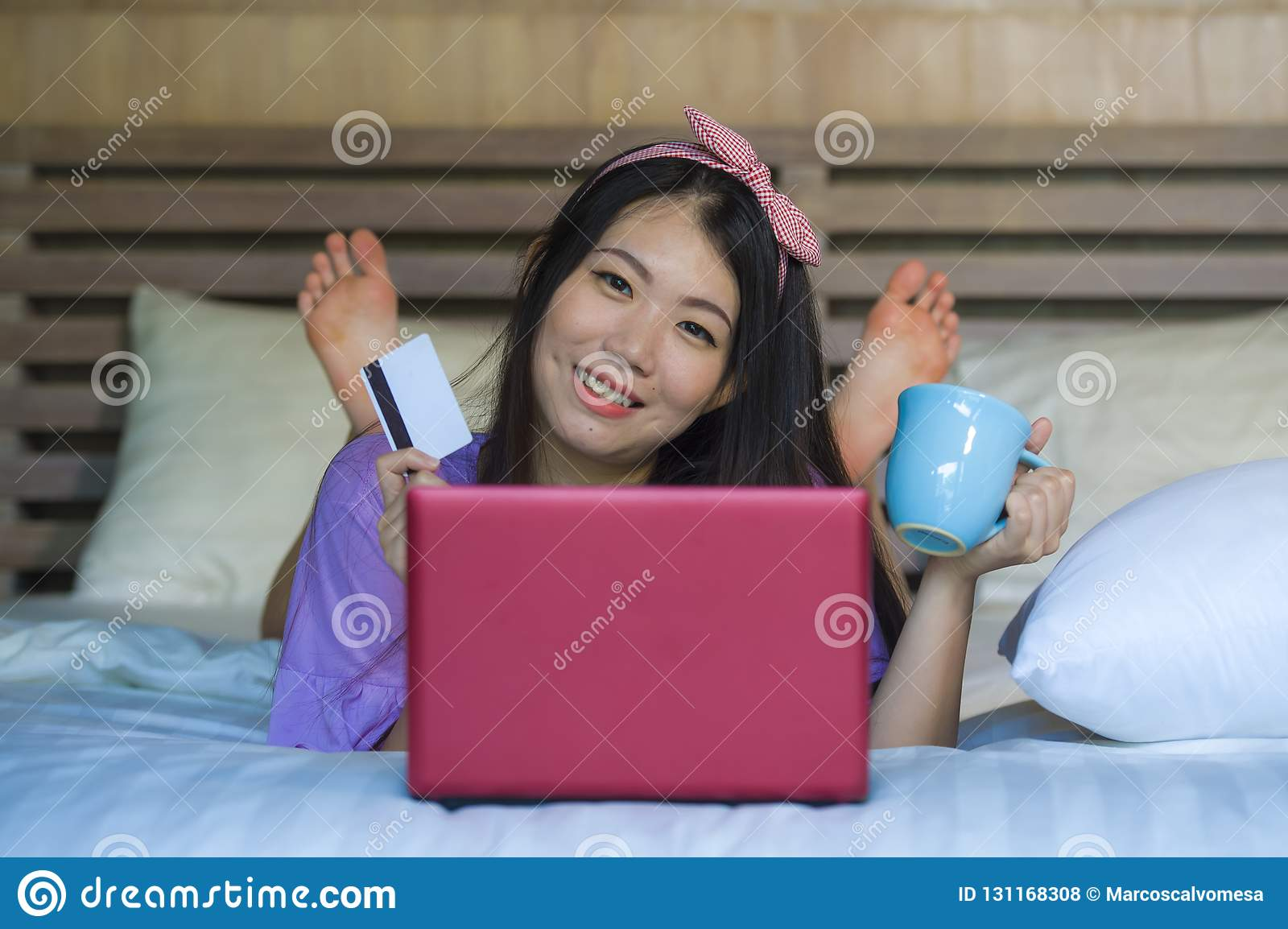 Young beautiful happy Asian Japanese woman using credit card internet banking on laptop computer at home in bed smiling shopping o