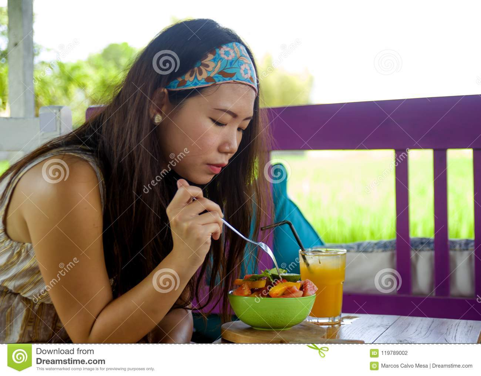 Young beautiful and happy Asian Korean woman drinking orange juice eating healthy salad at organic food coffee shop outdoors enjoy