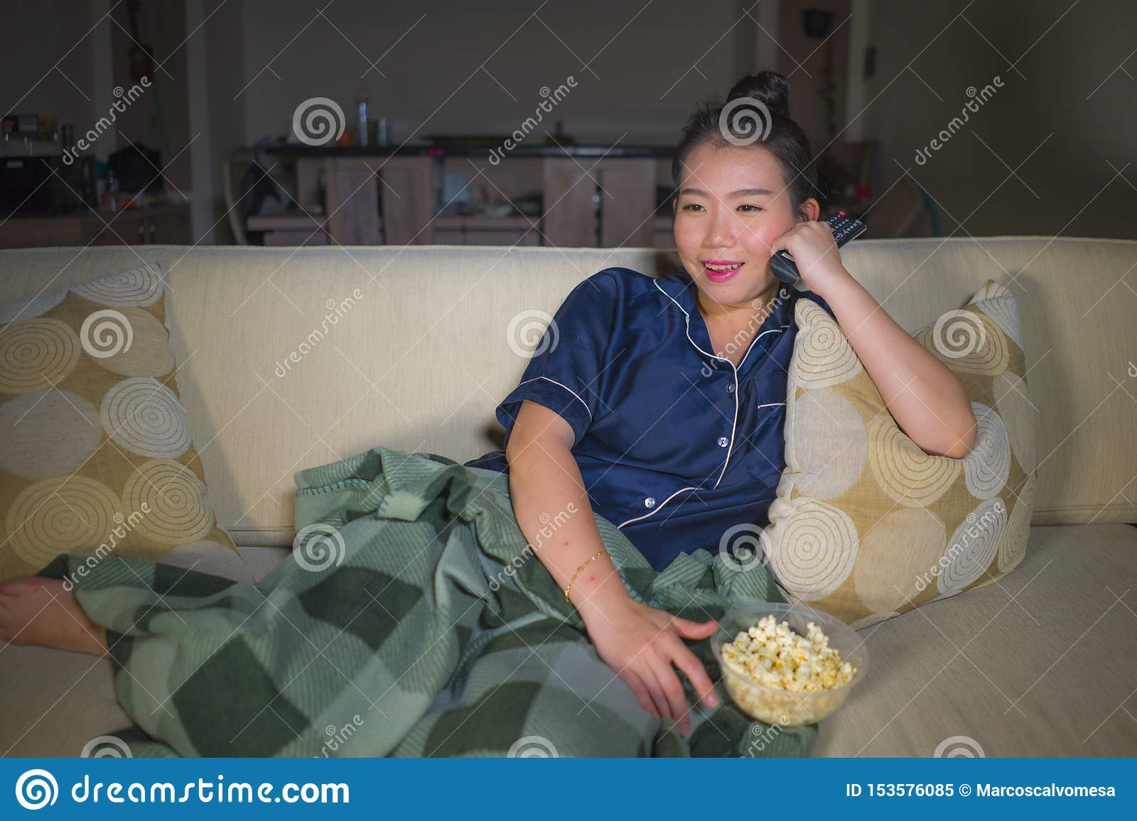 Young beautiful happy and relaxed Asian Chinese woman at home living room sitting cozy on sofa couch watching TV show episode or