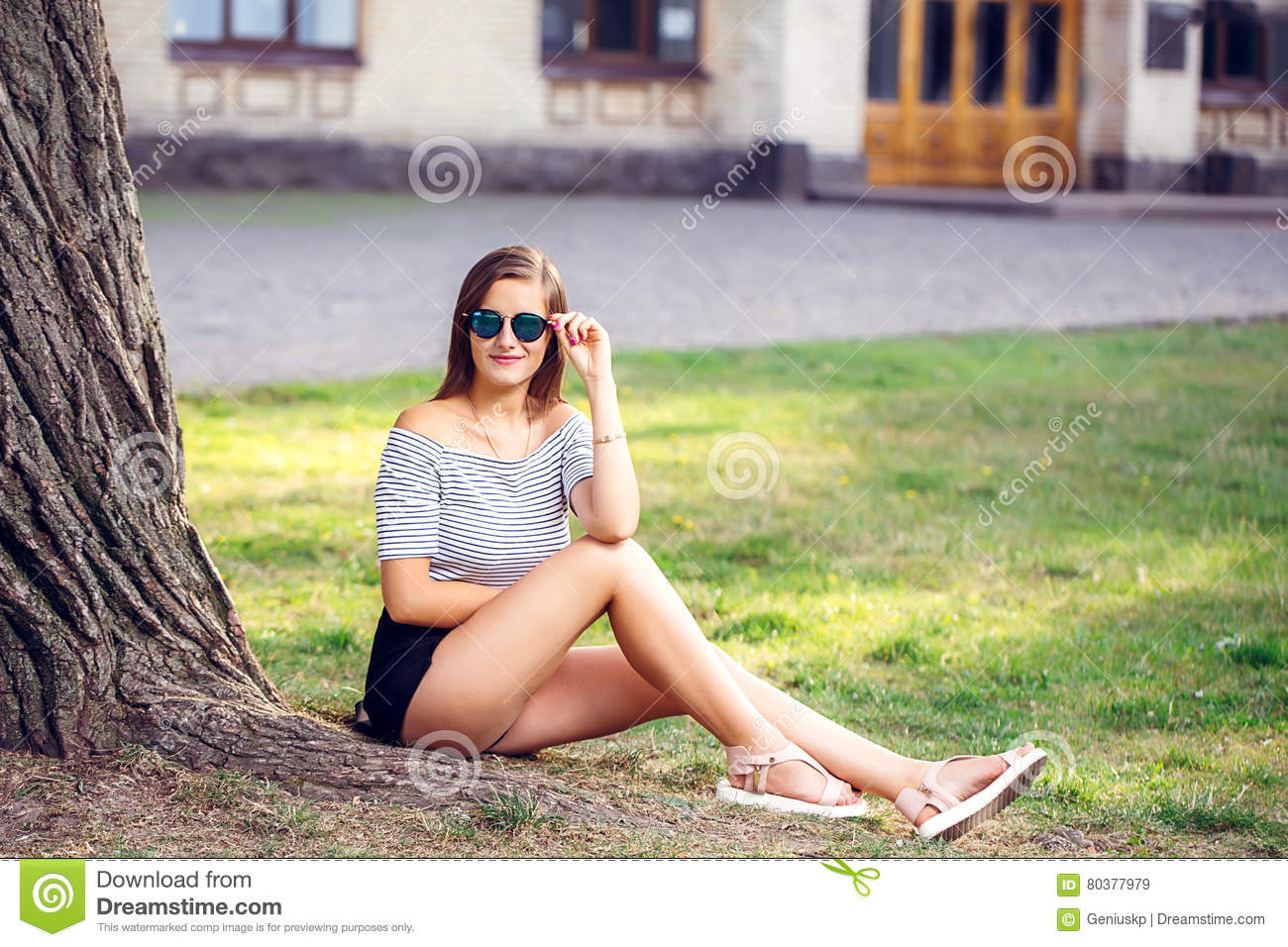 Young beautiful happy woman in round sunglasses sitting on the g