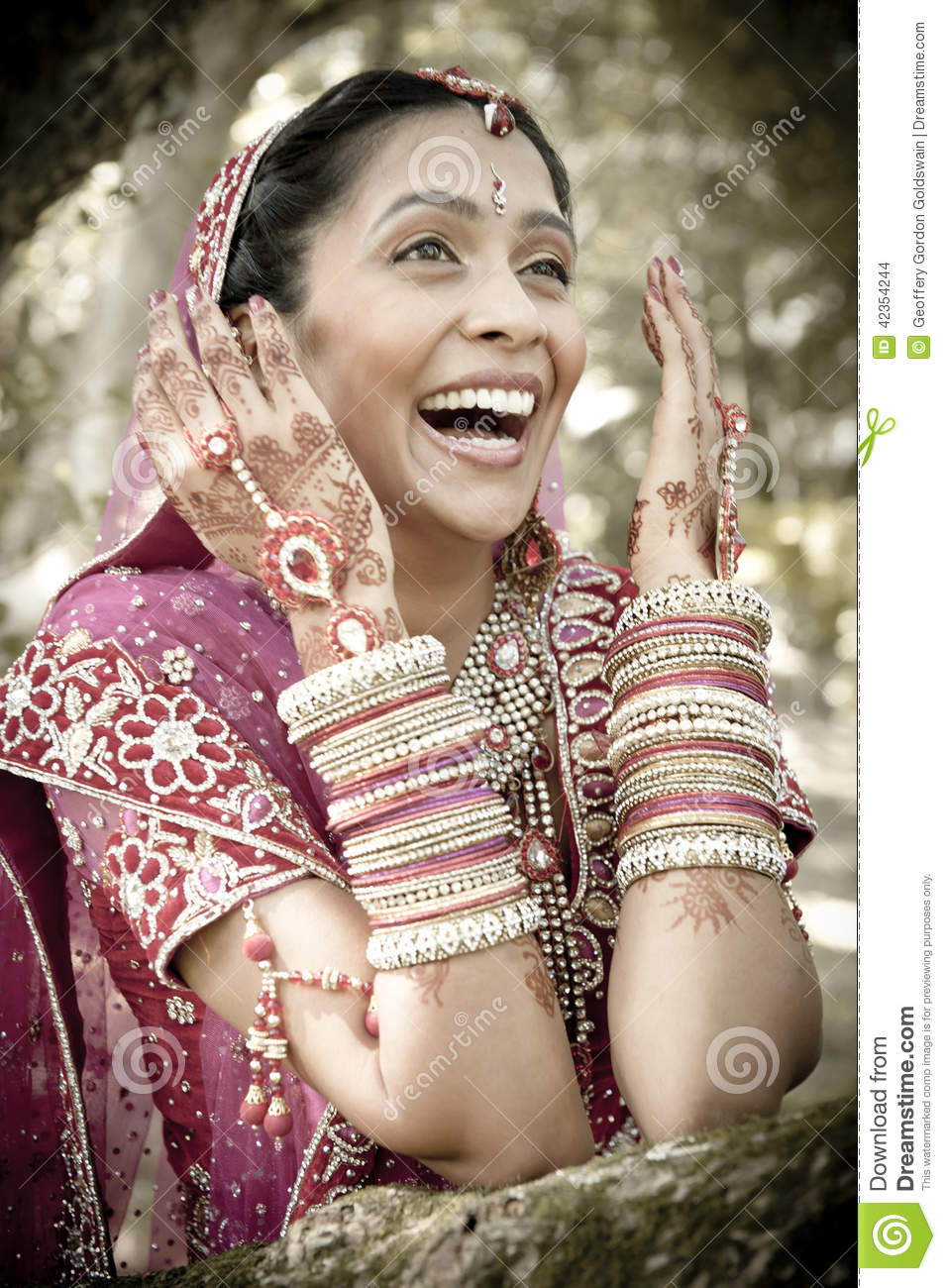 Young beautiful Indian Hindu bride laughing under tree with painted hands raised