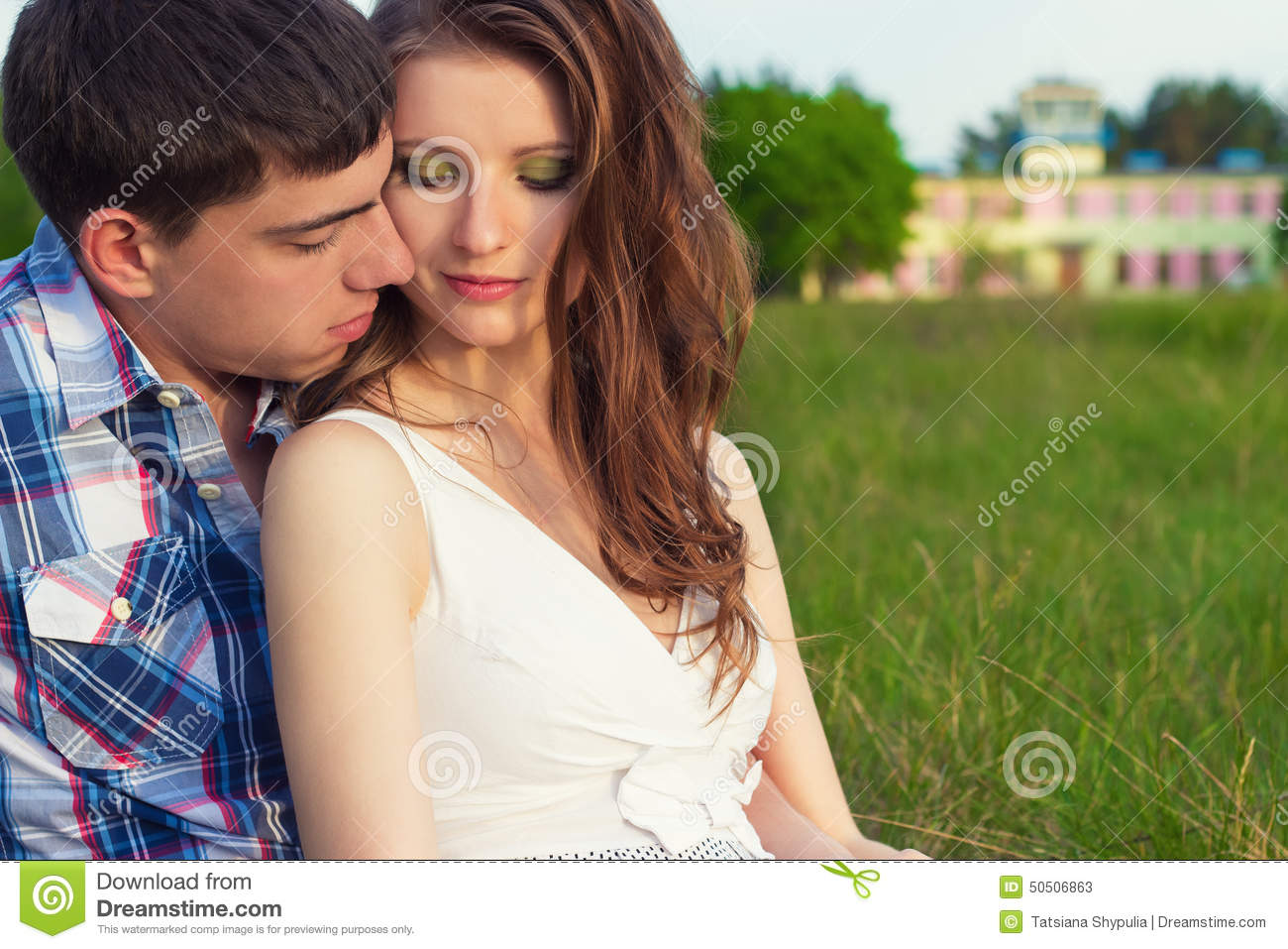 Young beautiful loving happy couple sitting in the box on the grass in the warm evening summer day