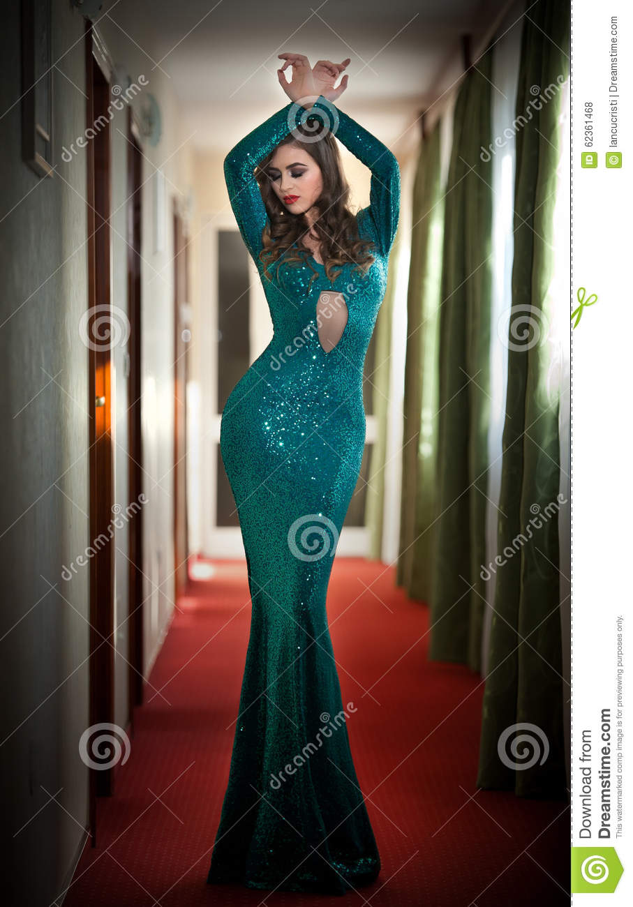 Young beautiful luxurious woman in long elegant turquoise dress posing indoors. Attractive brunette with tight fit glamorous dress