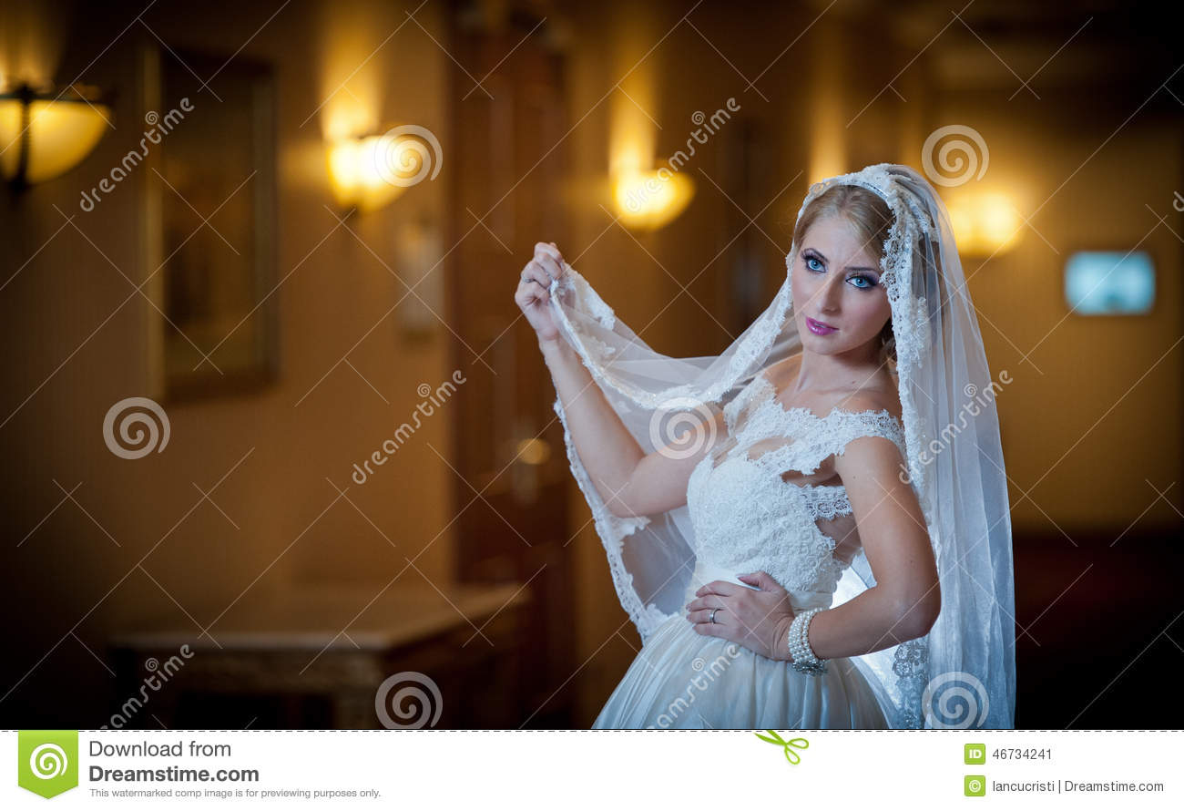 Young beautiful luxurious woman in wedding dress posing in luxurious interior. Gorgeous elegant bride with long veil. Seductive