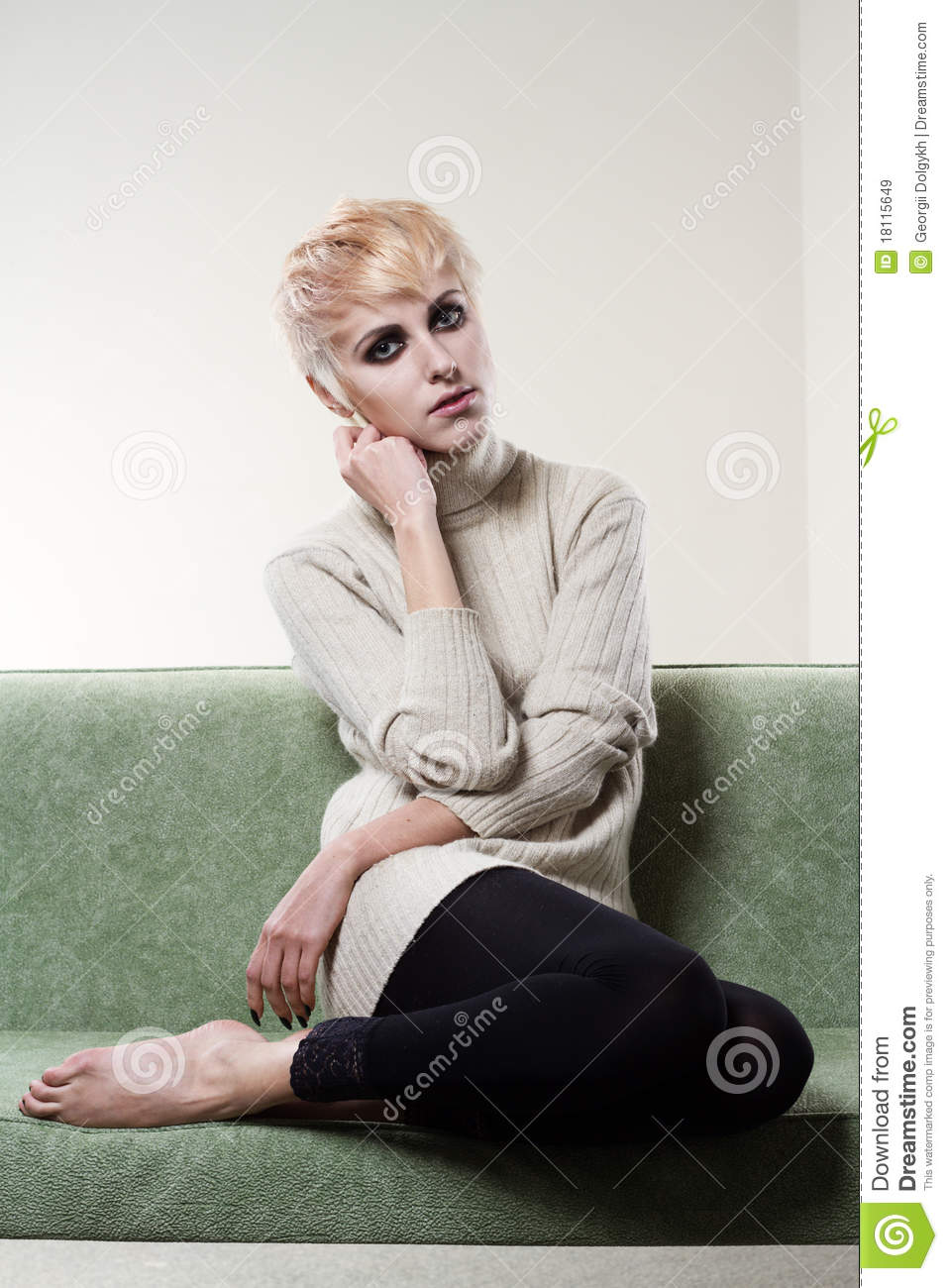 Cheerful model sitting on cosy couch text messaging ...