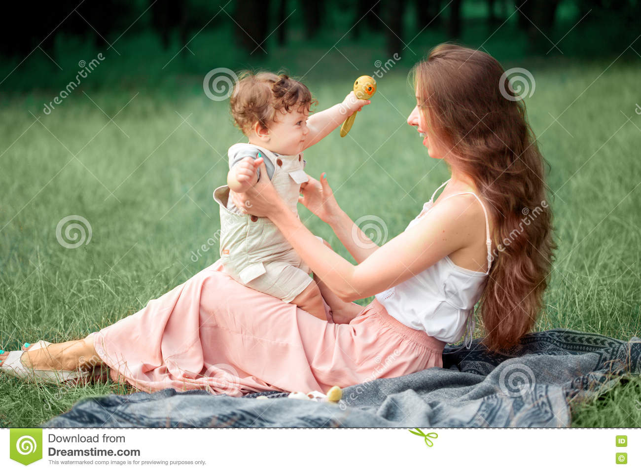 Young beautiful mother sitting with her little son against green grass. Happy woman with her baby boy on a summer sunny