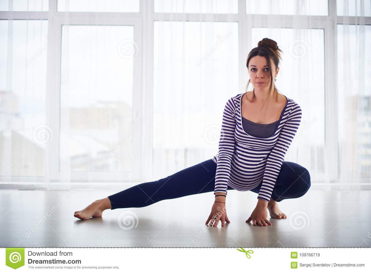 Young beautiful pregnant woman doing yoga asana at home.