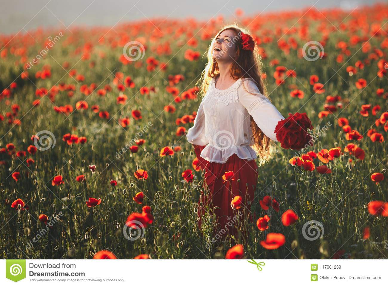 Young beautiful woman walking and dancing through a poppy field at sunset