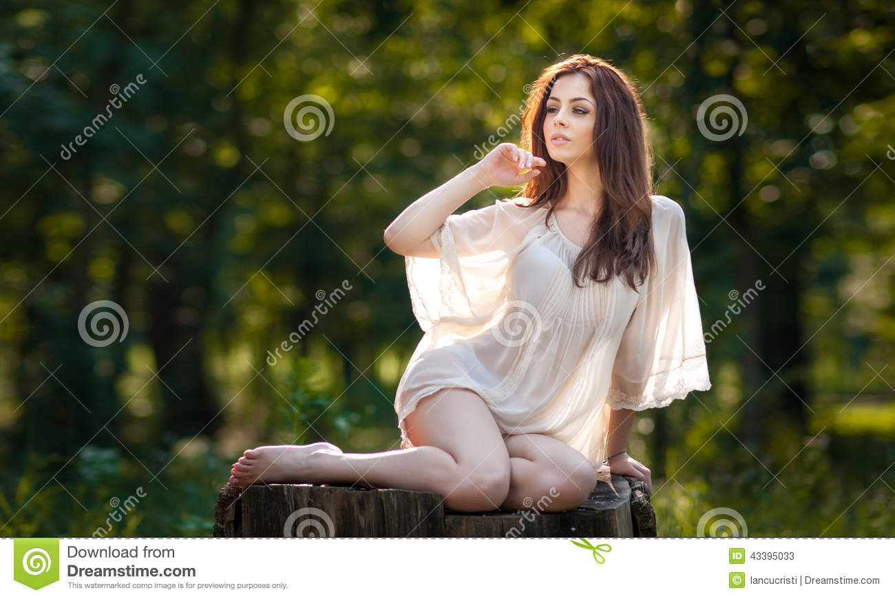 Young beautiful red hair woman wearing a transparent white blouse posing on a stump in a green forest. Fashionable girl