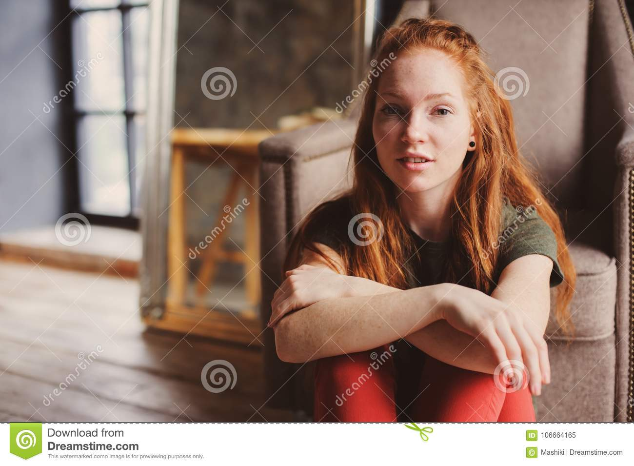 Redhead woman relaxing on rocking chair. Portrait of a beautiful redhead woman relaxing on