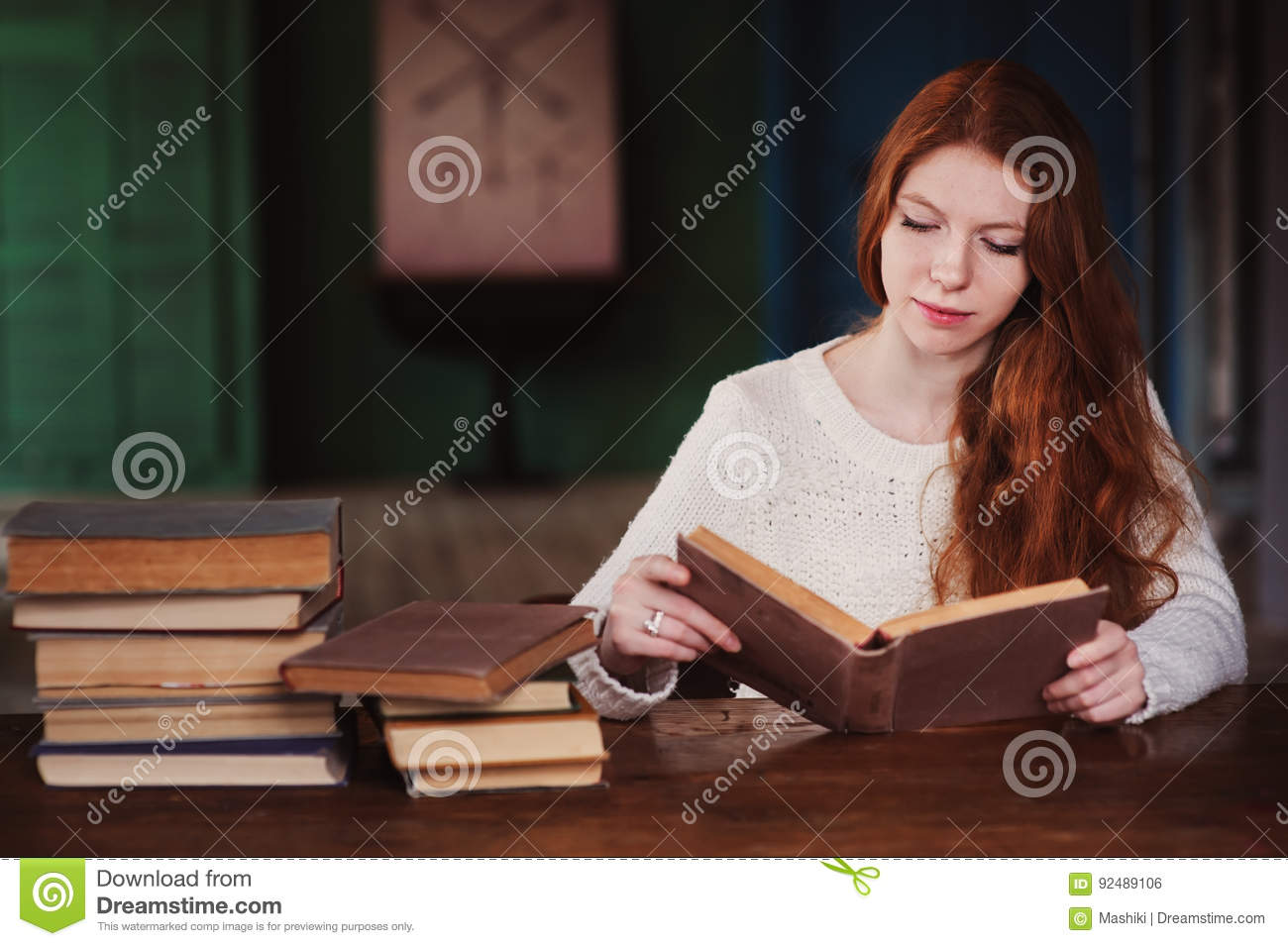 young beautiful redhead woman relaxing at home in the autumn cozy evening and reading book stock. Black Bedroom Furniture Sets. Home Design Ideas