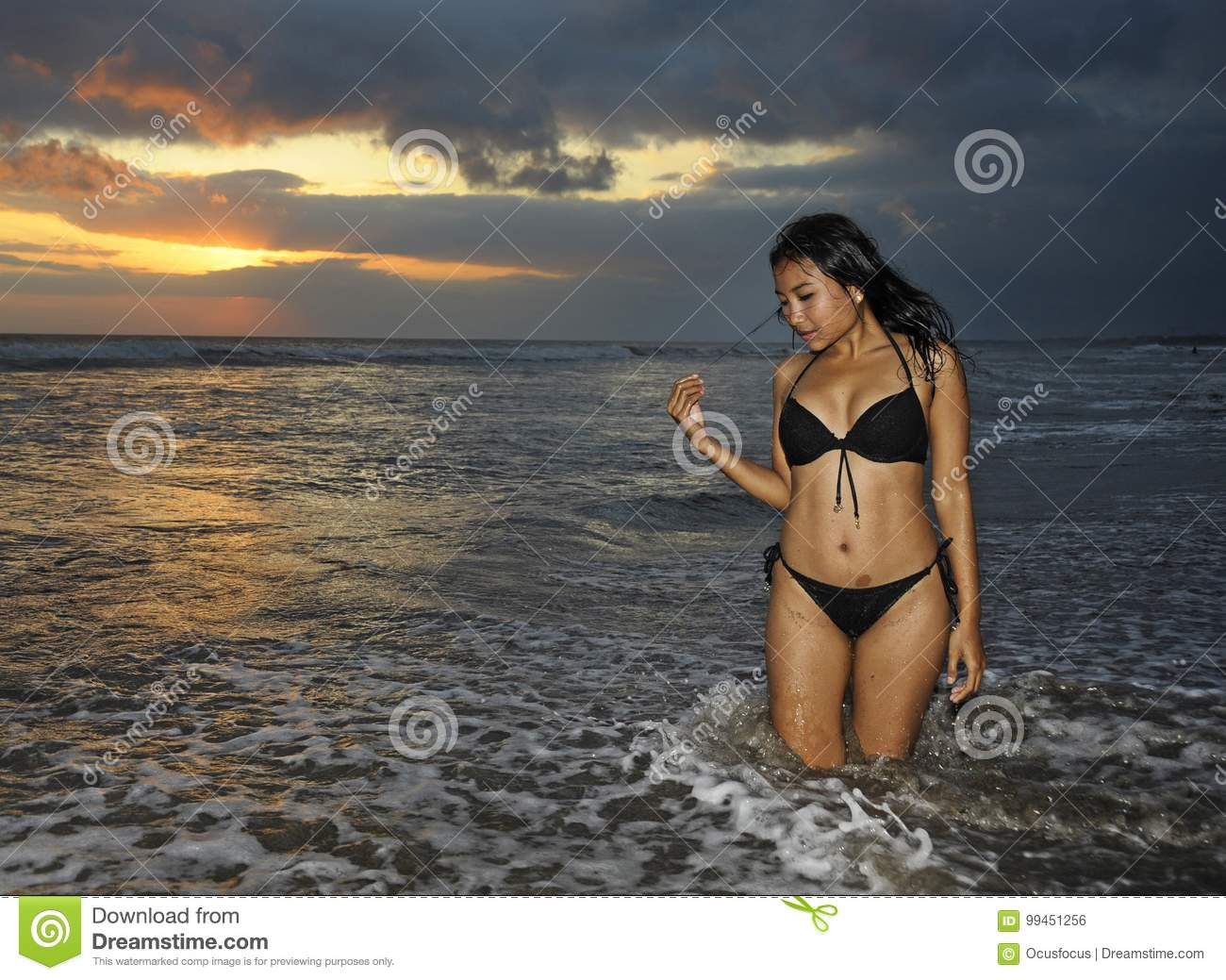 9185694610223 Young beautiful and asian woman in black bikini posing relaxed having fun  at sunset beach in