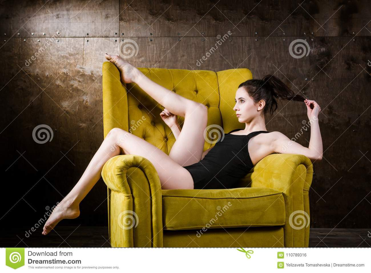 d592cb2d5 A young beautiful, Caucasian woman with thin figure and long bare legs,  barefoot posing