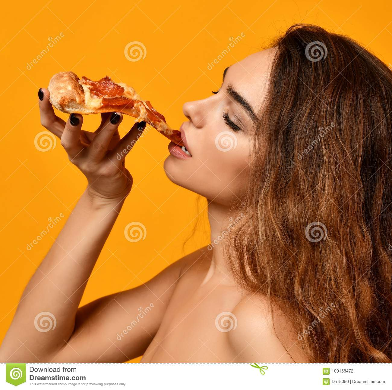 Young beautiful woman eat pepperoni pizza slice and hold whole pizza in box