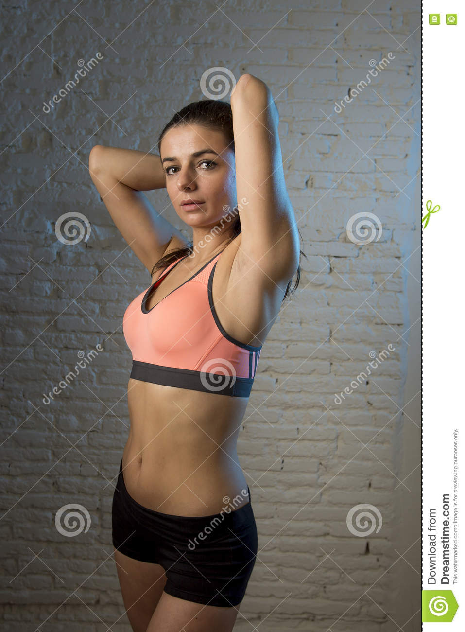 dd6c0b396 Young beautiful and woman in fitness top and shorts with perfect abdomen  posing on dim light interior background in healthy lifestyle sport and diet  concept