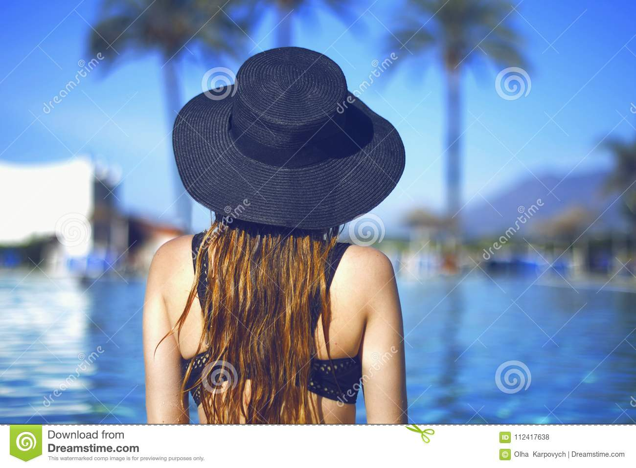 Young beautiful smile girl in black fashion hat, red lips and long hair, posing near pool beackground of palms.