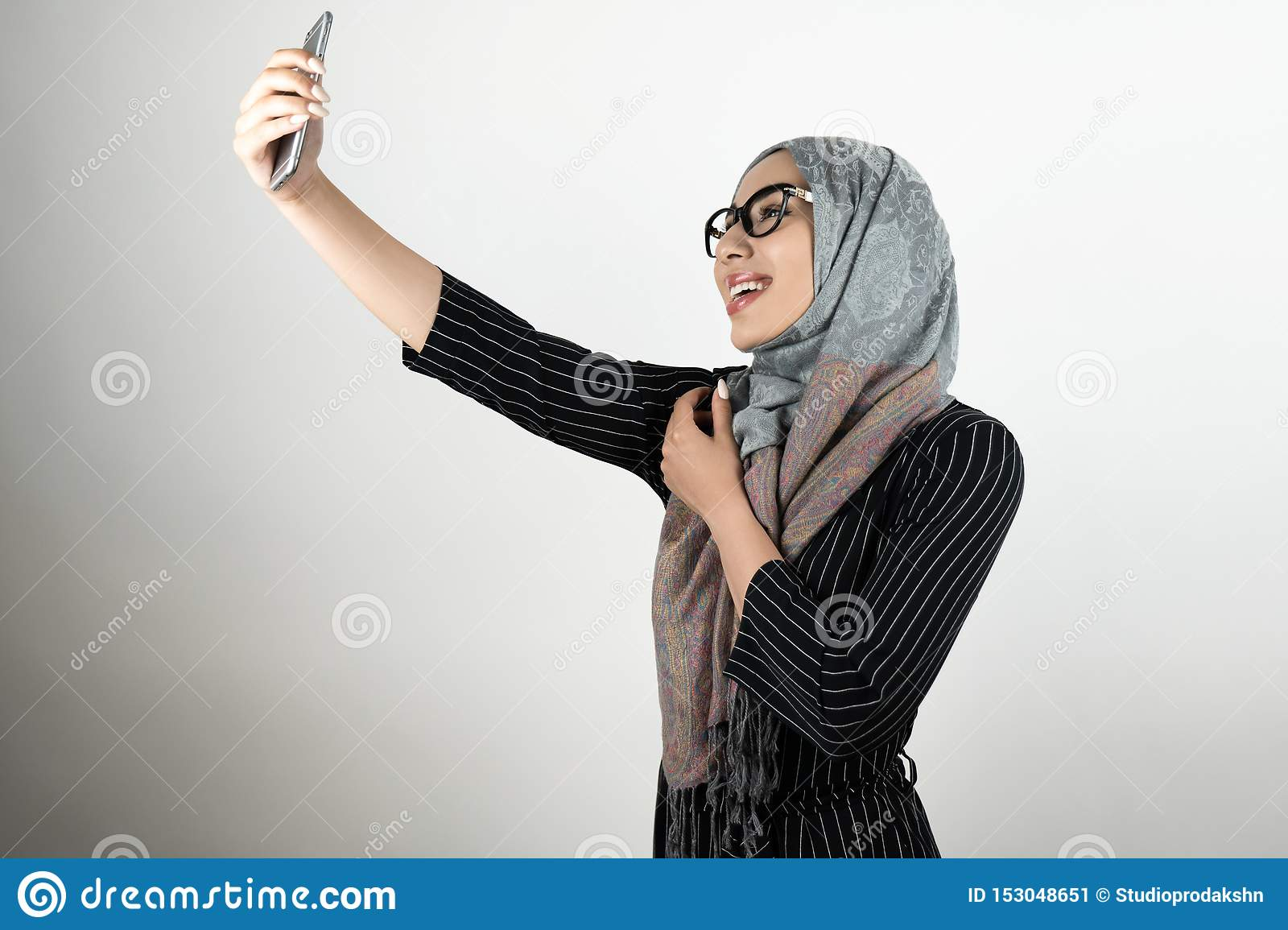 Young beautiful smiling Muslim woman in glasses wearing turban hijab, headscarf holding smartphone shooting a selfie