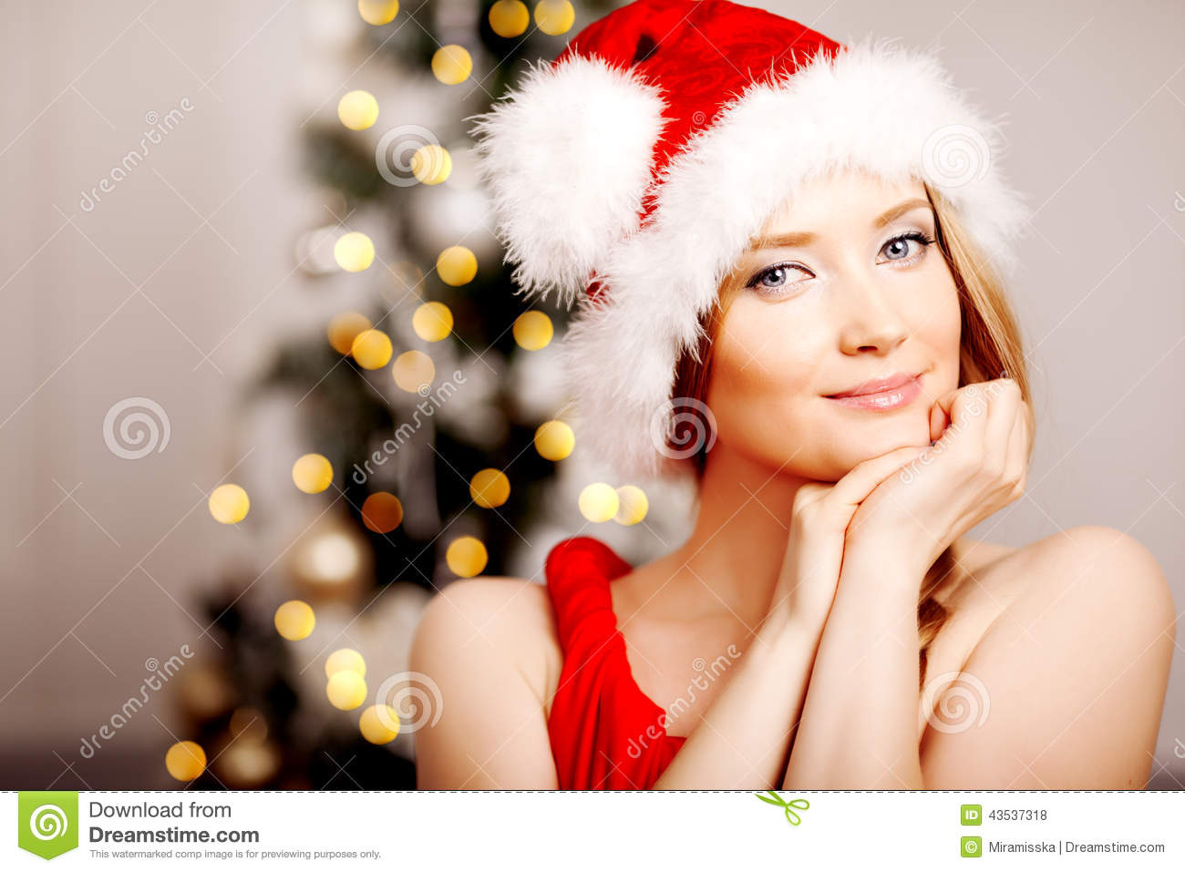 Young beautiful smiling santa woman near the Christmas tree. Fashionable luxury girl celebrating New Year. Beauty luxury trendy b
