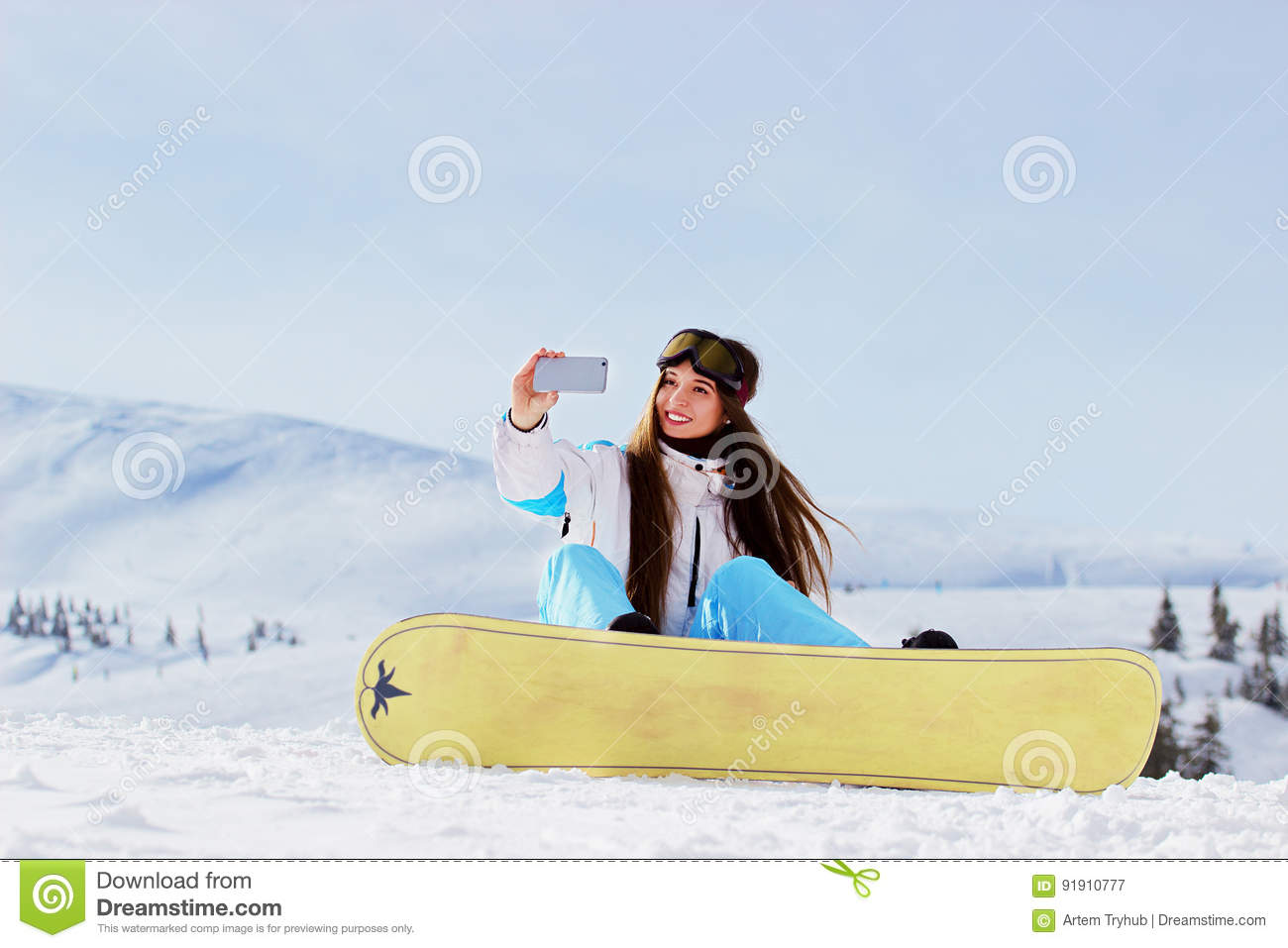 a2e13a7476 Young beautiful snowboarding girl with googles on her head taking selfie  with snowboard in the snowy
