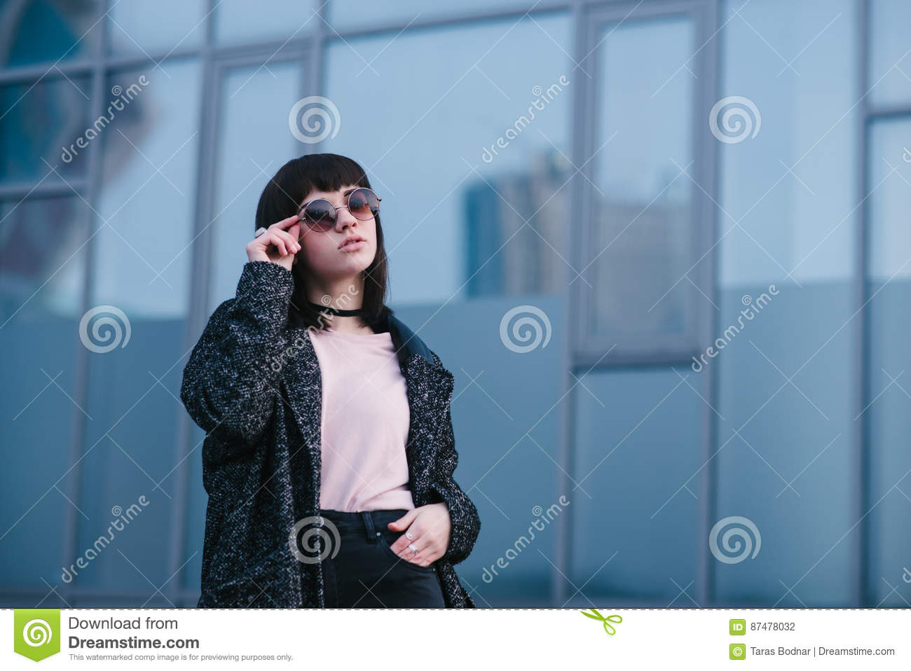 Young, beautiful and stylish dressed girl in the spring which adjusts his glasses and posing on urban background
