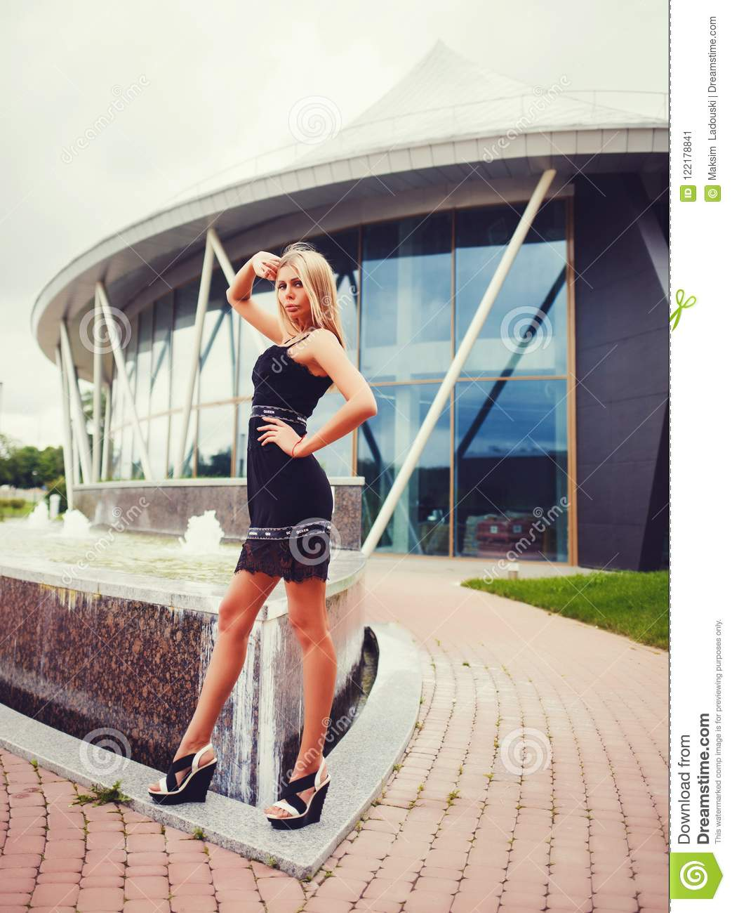Stylish girl with long legs posing at summer city