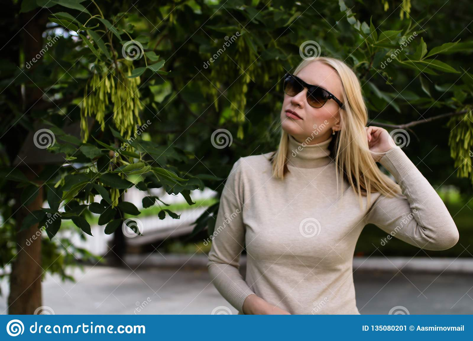 Young blond woman in sunglasses posing on the street