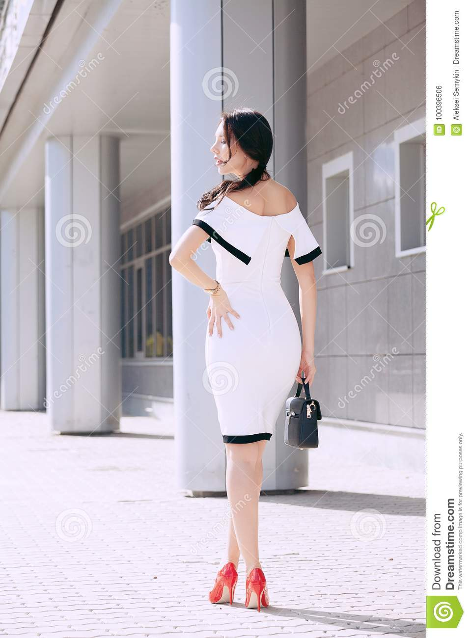 bc902790565 Young Beautiful Stylish Girl In White Dress And Black Bag Walking ...