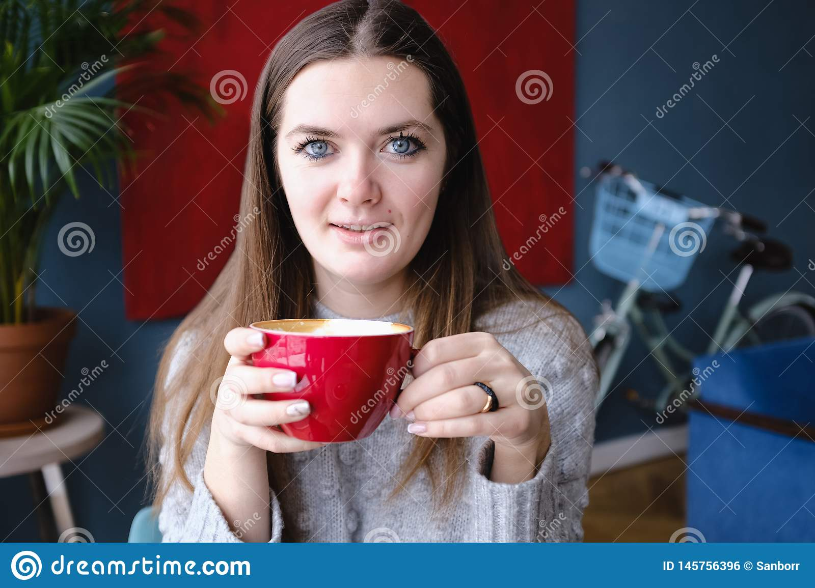 Young beautiful stylish woman sitting in a cafe, holding a Cup of cappuccino, looking at the camera, enjoying, city street,