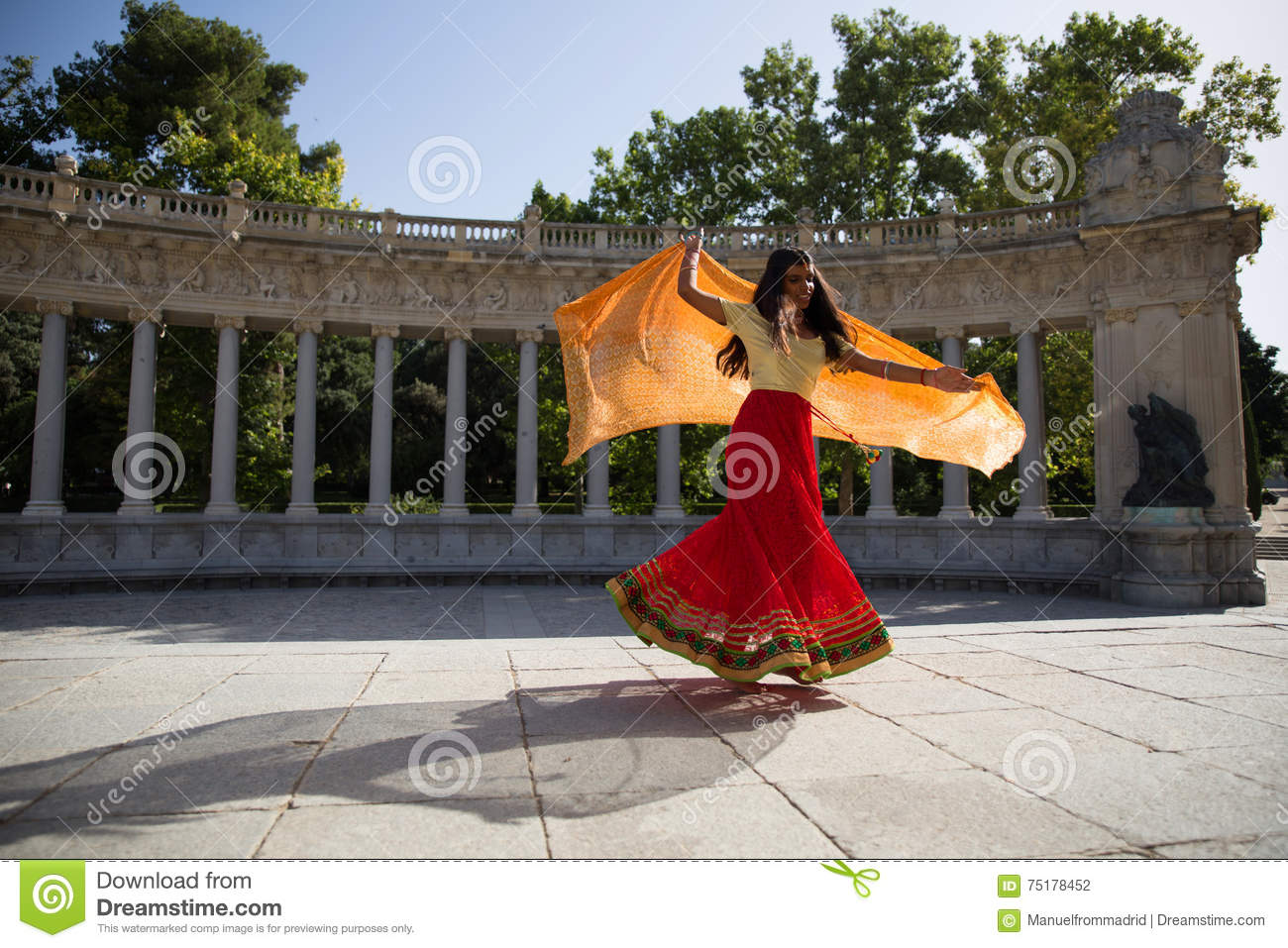 Young beautiful traditional indian woman dancing outdoors