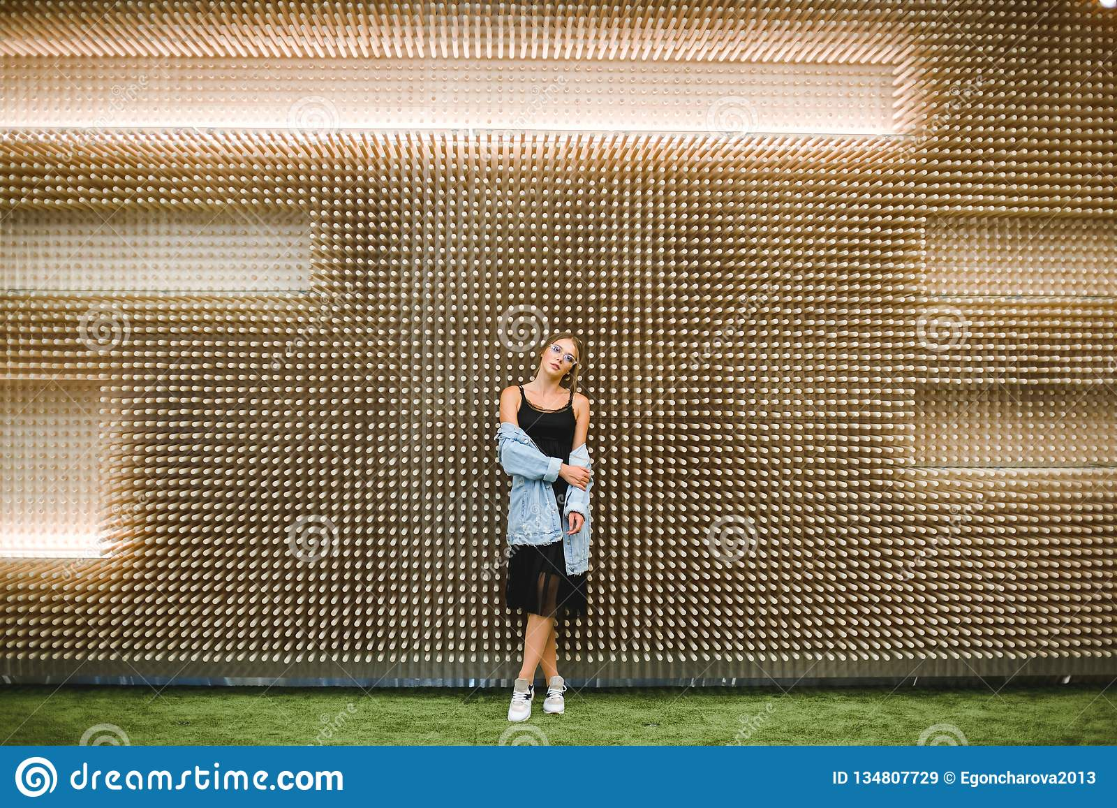 Young beautiful woman against the background of an unusual wooden wall.