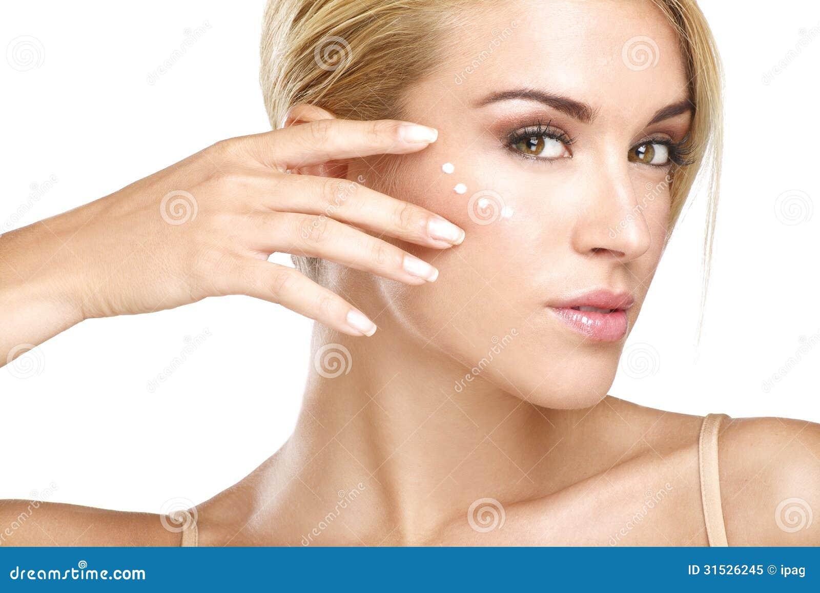 Young beautiful woman applying creme on her skin