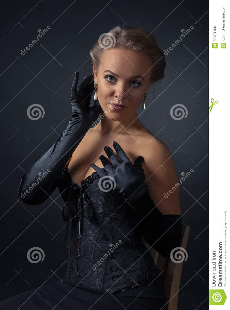 Young Beautiful Woman In Black Corset With Pearl Earrings