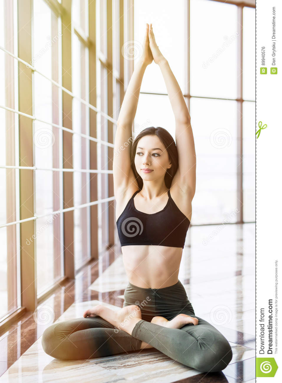 Young beautiful woman doing yoga padmasana in yoga studio. Sport health concept.