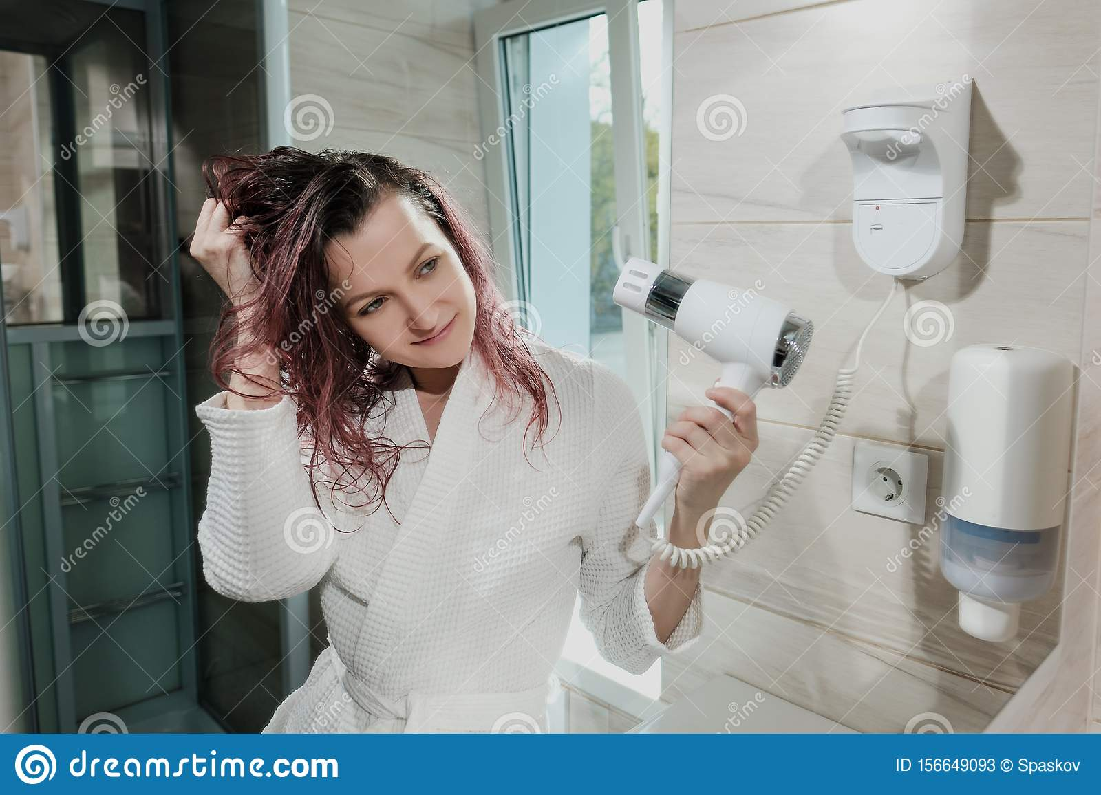 Young beautiful woman with dyed hair in white bathrobe in bathroom dries hair with hairdryer and smiles.