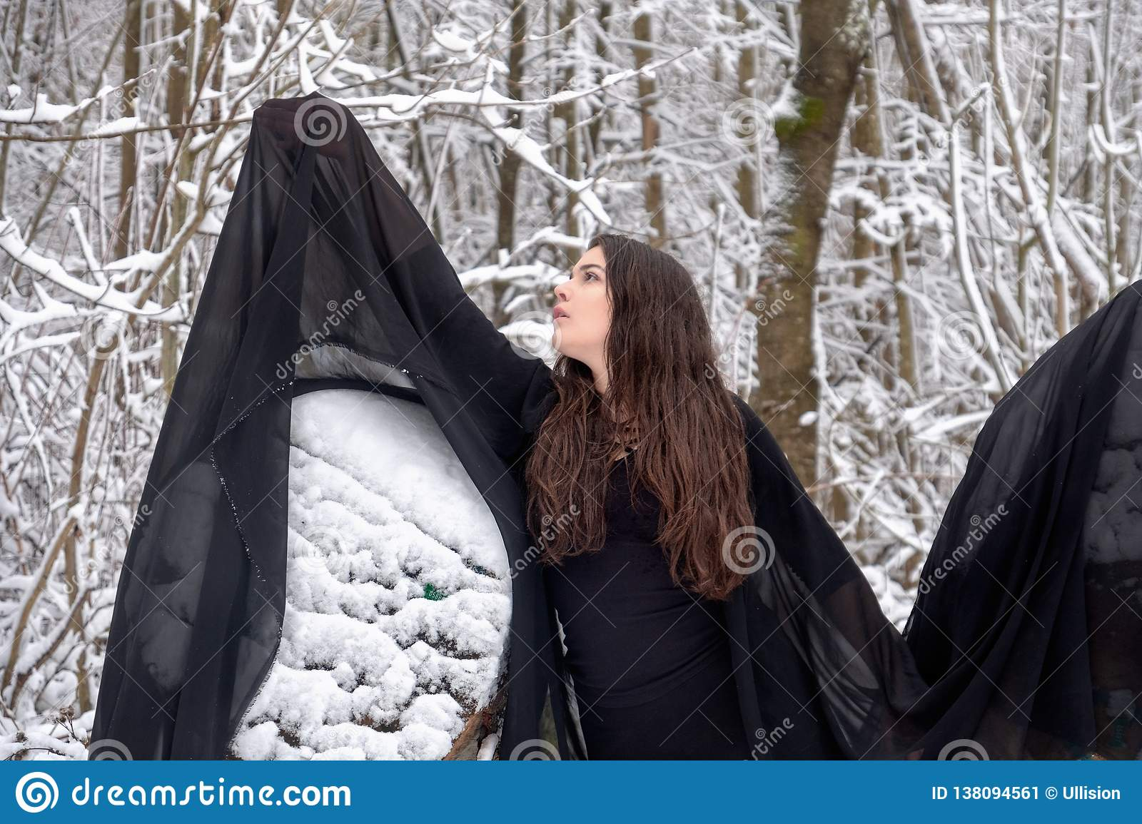 Young beautiful woman girl ballet presents herself in snowy winter forest