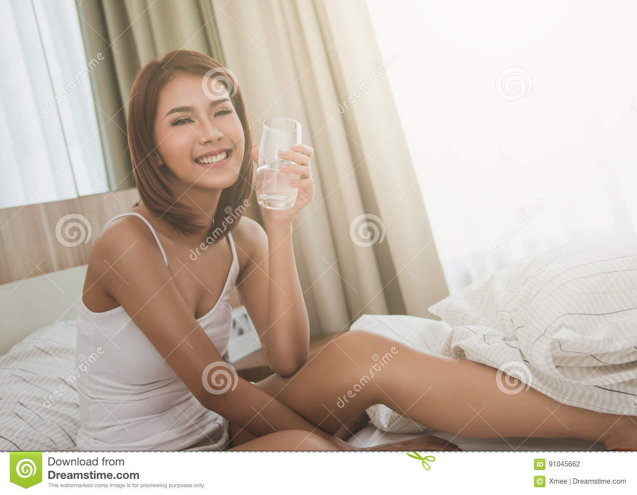 Young beautiful woman with glass of water in a bed. Smiling woman laying in the hotel room,bedroom.