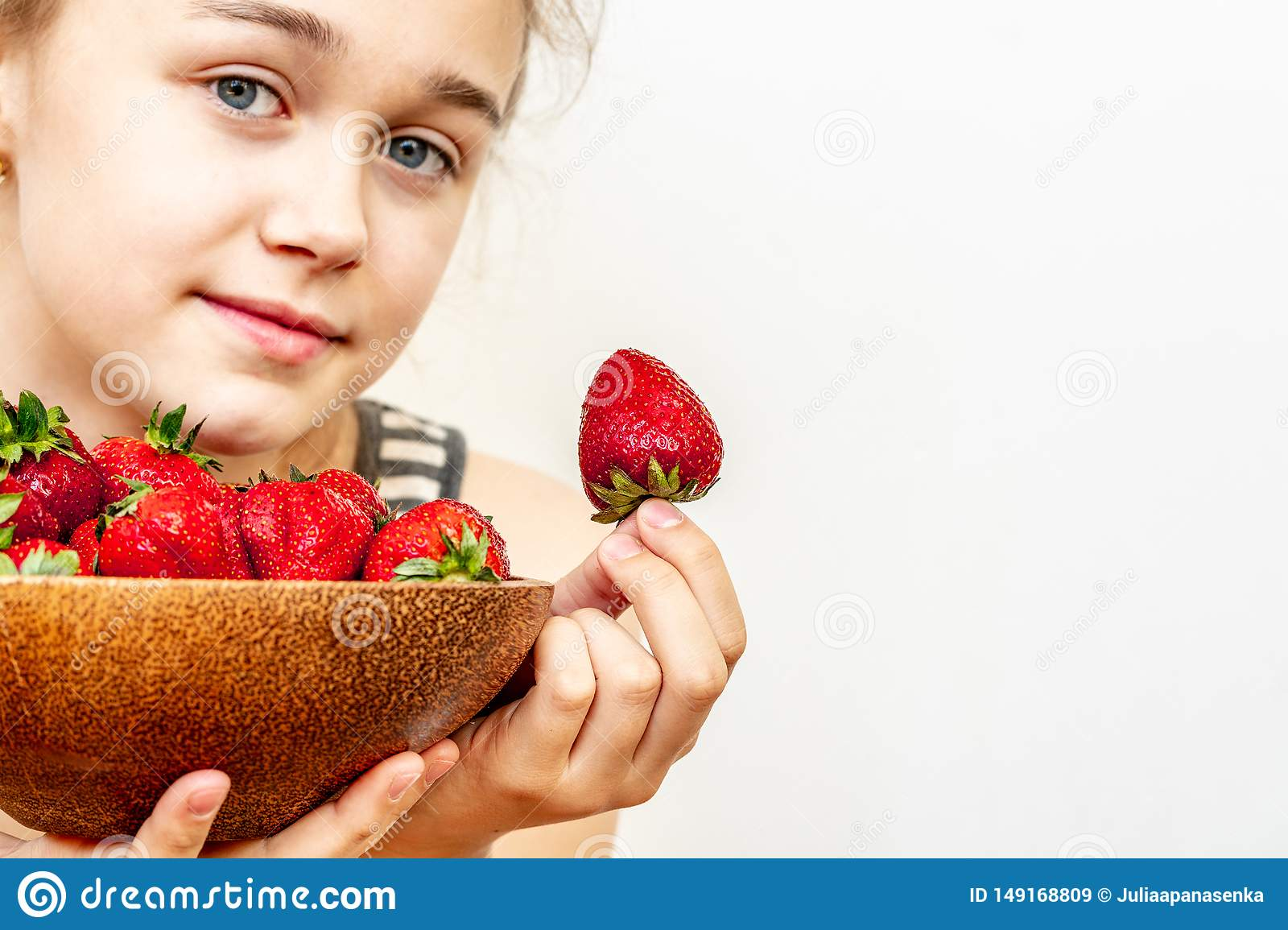 A young woman is holding a bowl of strawberries