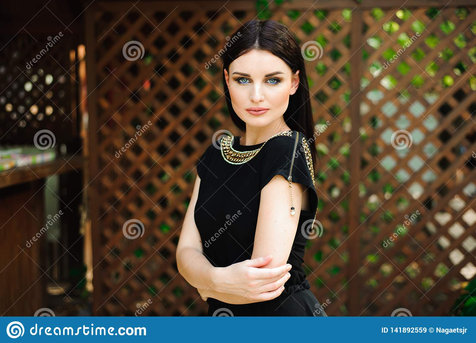 Young beautiful woman in long black evening dress walking path in park. Fashion style portrait of gorgeous beautiful