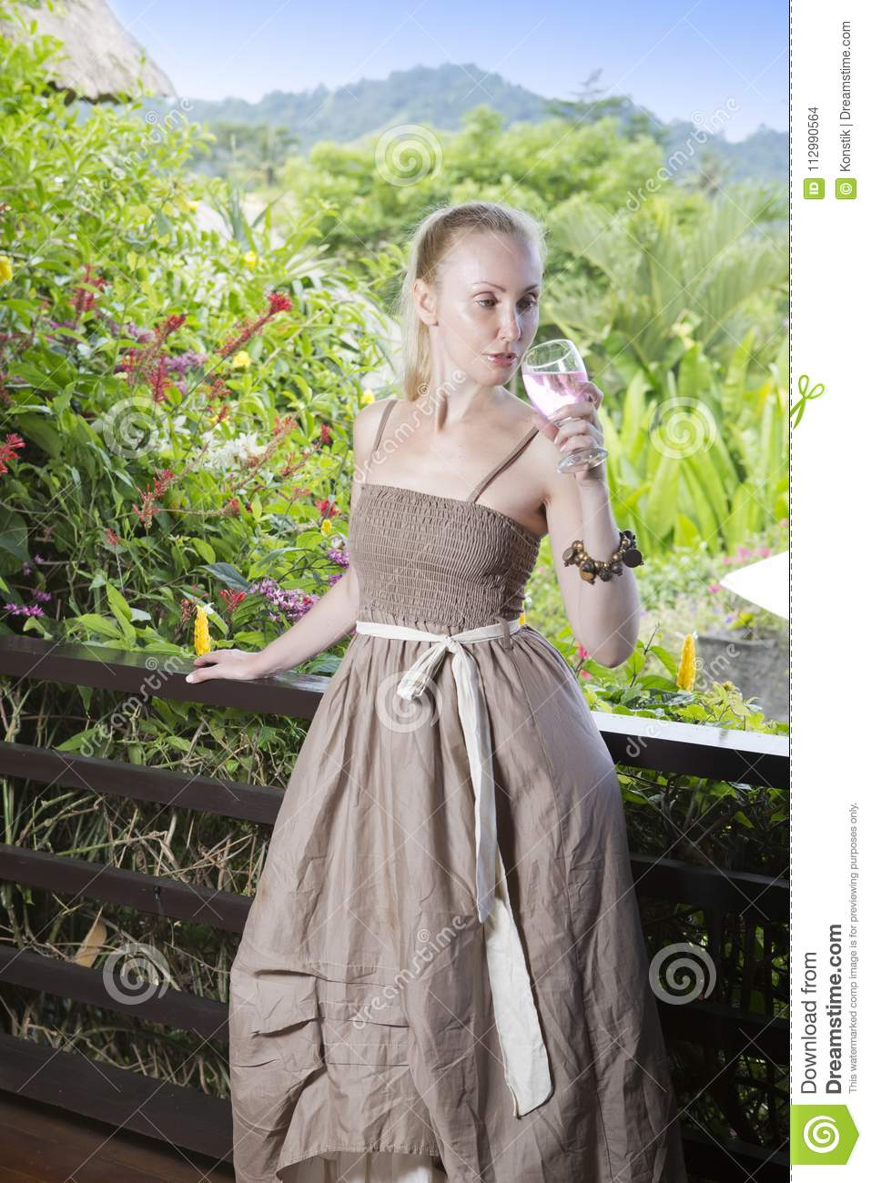The young beautiful woman in a long dress with a glass of wine looks at the tropical nature